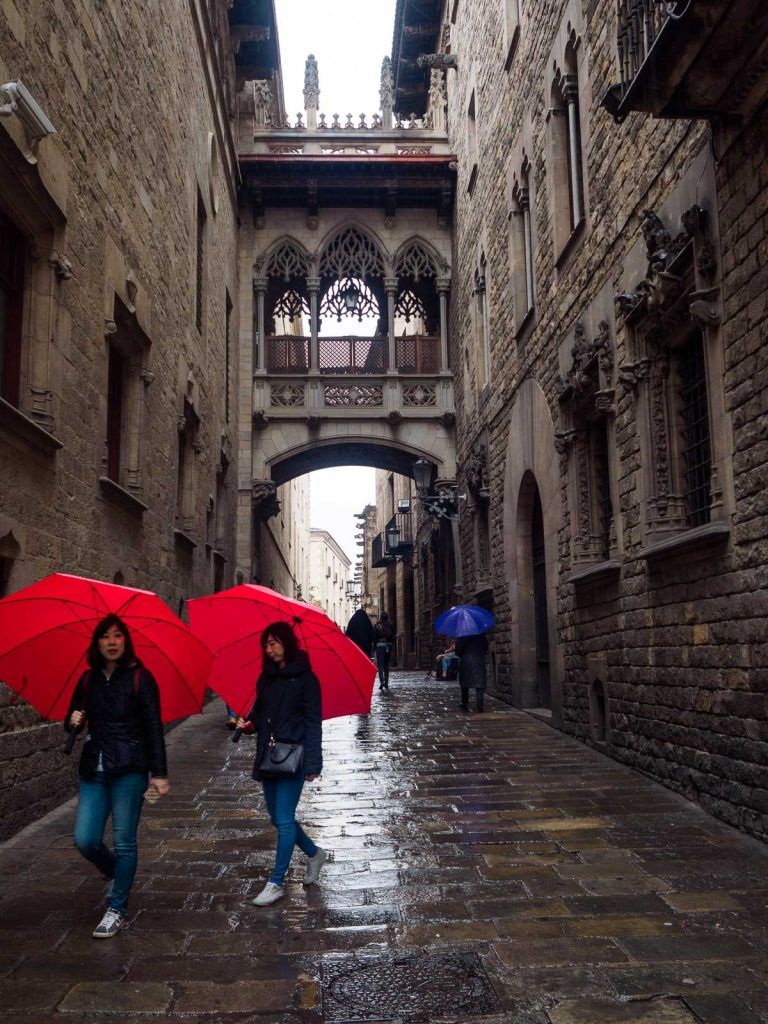 Two oriental tourist women walk through Barcelona Gothic Quartier, under the rain and the arch in Carrer del Bisbe (Bishop Street), carrying same red umbrellas from their hotel.